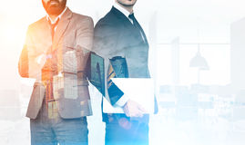 Two businessmen in office with skyscrapers, toned Royalty Free Stock Photo