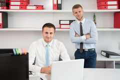 Two Businessmen In An Office Smiling Stock Photo
