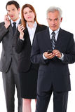 Two businessmen and one businesswoman with mobile Royalty Free Stock Photography