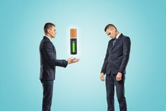 Two businessmen, one posing as if manually controlling the battery suspended in the air, the other standing half-turned. With a sad expression on his face stock photos