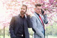 Two businessmen outside talking on the phone Royalty Free Stock Image