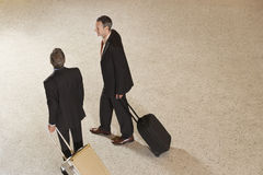 Two Businessmen Pulling Suitcases In Lobby. Elevated view of two businessmen pulling suitcases in airport lobby Stock Photo