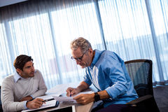 Two businessmen reading a document and interacting Stock Photography