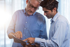 Two businessmen reading a document and interacting Royalty Free Stock Photo