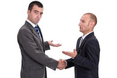 Two businessmen rejecting the responsibility and absolving thems. Elves of guilt with a handshake, isolated on white Stock Images