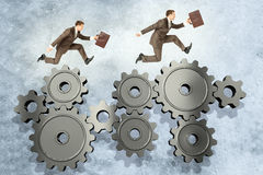 Two businessmen running on wheel gears Stock Photo