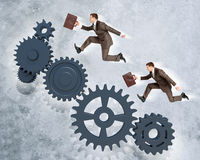 Two businessmen running on wheel gears Royalty Free Stock Photography