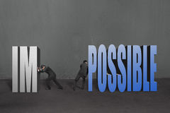 Two businessmen separate word. Impossible to IM and POSSIBLE; to make it possible in concrete wall background Royalty Free Stock Images