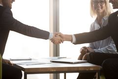Satisfied business partners in suits shake hands, close up view. Two businessmen shake hands at meeting, satisfied business partners in suits handshaking after royalty free stock photo