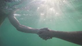 Two businessmen shake hands under water through the sun. close up. 1920x1080. Two businessmen shake hands under water. 1920x1080, hd stock video footage
