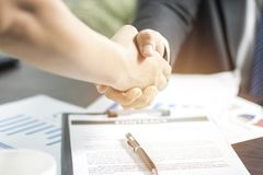 Two businessmen shaking hand after successful negotiate and sign. Ing on contract about working and partner together on working table in office stock photo