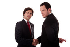 Two businessmen shaking hands. And one businessman with his fingers crossed behind his back and smiling, isolated on white background Stock Photography