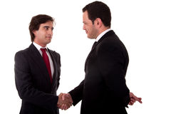 Two businessmen shaking hands. And one businessman with his fingers crossed behind his back and smiling Royalty Free Stock Photo