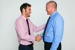 Two businessmen shaking hands. Photo of two businessmen shaking hands against a plain background, part of a series see my portfolio for images of them fighting Stock Photos