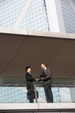 Two Businessmen Shaking Hands. Outside Office Building Stock Photo