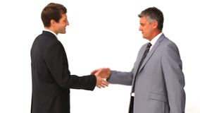 Two businessmen shaking hands. Against a white background stock video
