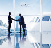 Two Businessmen Shaking Hands In An Airport Royalty Free Stock Photos