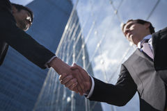 Two businessmen shaking hands in Beijing, China, view from below stock photos