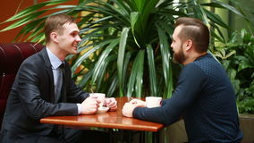 Two businessmen shaking hands in a cafe. Discuss business and drink coffee stock video footage