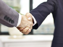 Two businessmen shaking hands. Close-up, low angle view of a firm handshake in office by two asian businessmen Stock Photography
