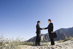 Two Businessmen Shaking Hands In Desert Royalty Free Stock Photos
