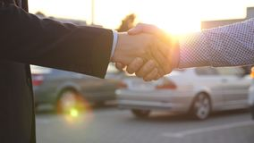 Two businessmen shaking hands of each other with cars in parking at background. Handshake between manager or dealer and. Client. Shaking of male arms outside stock video footage