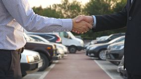 Two businessmen shaking hands of each other with cars in parking at background. Handshake between manager or dealer and. Client. Shaking of male arms outside stock video