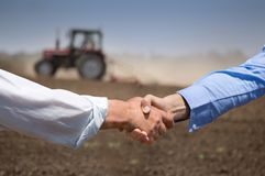 Farmers shking hands in front of tractor. Two businessmen shaking hands in field with tractor working in background. Agribusiness concept stock image