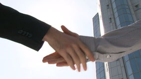 Two businessmen shaking hands. In front of office building stock video