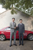 Two Businessmen Shaking Hands In Front of Red Car Stock Photos