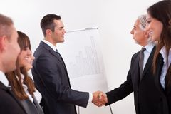 Two businessmen shaking hands. In greeting and congratulations during an introductory line up of young staff in an office Royalty Free Stock Photos