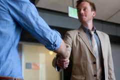 Two businessmen shaking hands. At office Stock Photo