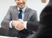 Two businessmen shaking hands in office. Businesss and office concept - two businessmen shaking hands in office Royalty Free Stock Images