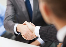 Two businessmen shaking hands in office. Businesss and office concept - two businessmen shaking hands in office Stock Photo