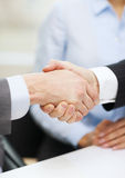 Two businessmen shaking hands in office. Businesss and office concept - two businessmen shaking hands in office Royalty Free Stock Photos