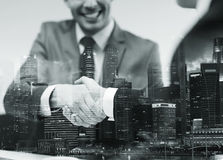 Two businessmen shaking hands at office. Business, cooperation, partnership and people concept - two businessmen shaking hands at office over city buildings and Royalty Free Stock Photos