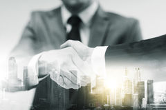 Two businessmen shaking hands at office. Business, cooperation, partnership and people concept - two businessmen shaking hands at office over city buildings and Stock Photo