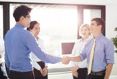 Businessmen Shaking Hands In Office Stock Photography