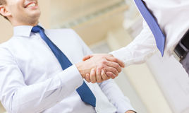 Two businessmen shaking hands in office. Businesss and office concept - two businessmen shaking hands in office Royalty Free Stock Photo