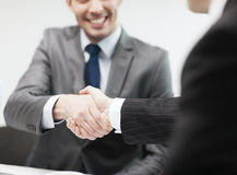 Two businessmen shaking hands in office. Businesss and office concept - two businessmen shaking hands in office Stock Photos