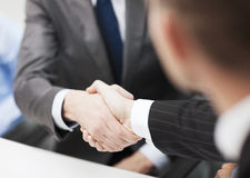Two businessmen shaking hands in office. Businesss and office concept - two businessmen shaking hands in office Stock Images
