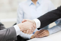 Two businessmen shaking hands in office. Businesss and office concept - two businessmen shaking hands in office Stock Image