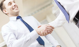 Two businessmen shaking hands in office. Businesss and office concept - two businessmen shaking hands in office Royalty Free Stock Image