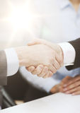 Two businessmen shaking hands in office Stock Photos