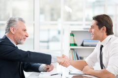 Two businessmen shaking hands in office Stock Images
