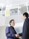 Two Businessmen Shaking Hands In Office. Low angle view of two businessmen shaking hands in office atrium Royalty Free Stock Photography