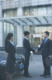 Two businessmen shaking hands outside behind a glass wall Royalty Free Stock Photo