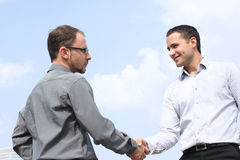 Two businessmen shaking hands on sky background. Closeup of two young businessmen shaking hands over a deal on sky background stock photos