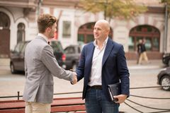 Two businessmen shaking hands while standing in front of a classic European building. Outdoors Royalty Free Stock Photos