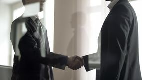 Two businessmen shaking hands to each other, confirming deal, view through glass. Stock photo royalty free stock photo